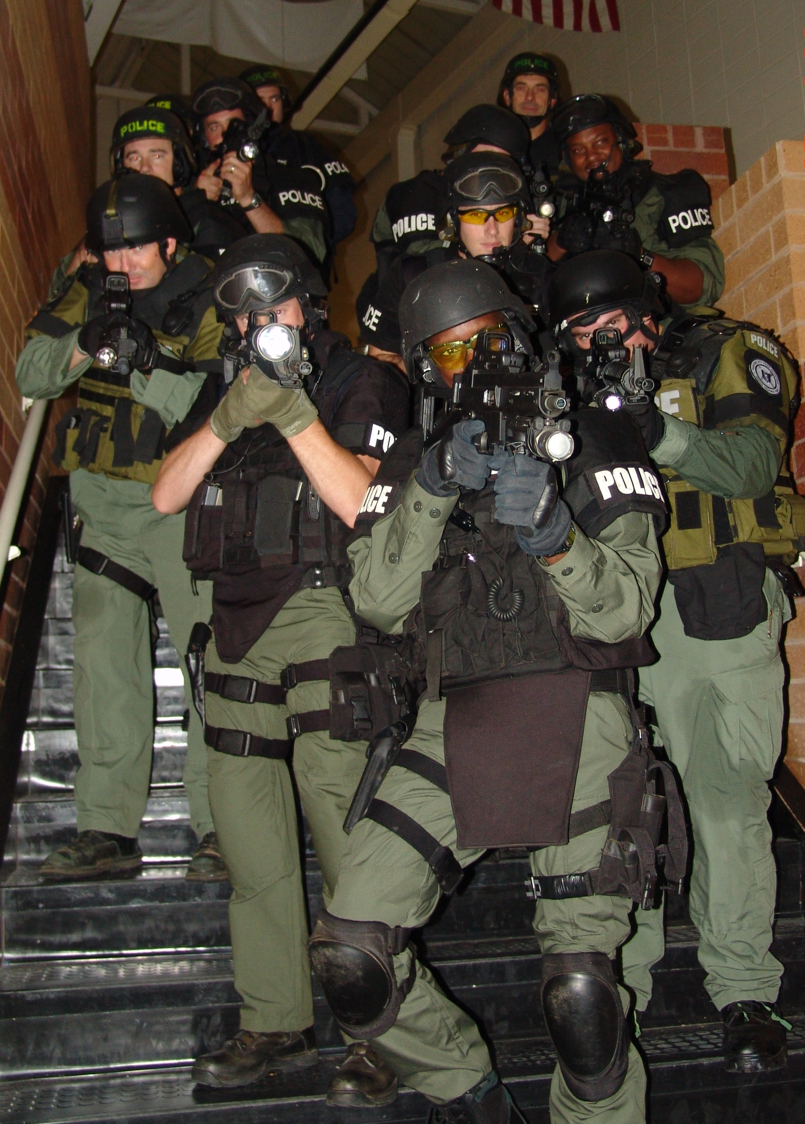 SWAT Team in Full Gearl Hold Up Weapons on Staircase