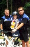 Corporal Jay Hughes and Corporal Terry Blackburn with Child on Bicycle