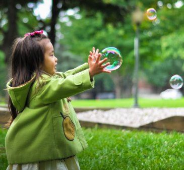 Girl in park with bubbles by Leo Rivas